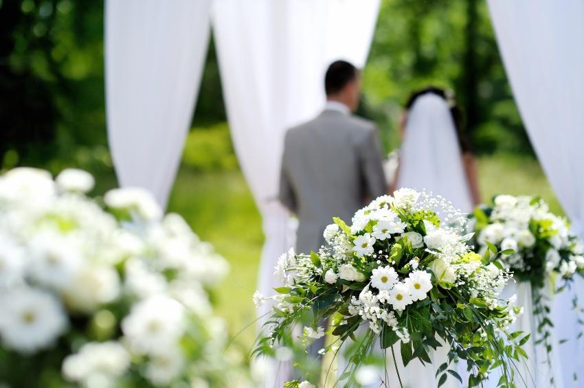 Blumendekoration einer Hochzeit - im Hintergrund das Brautpaar