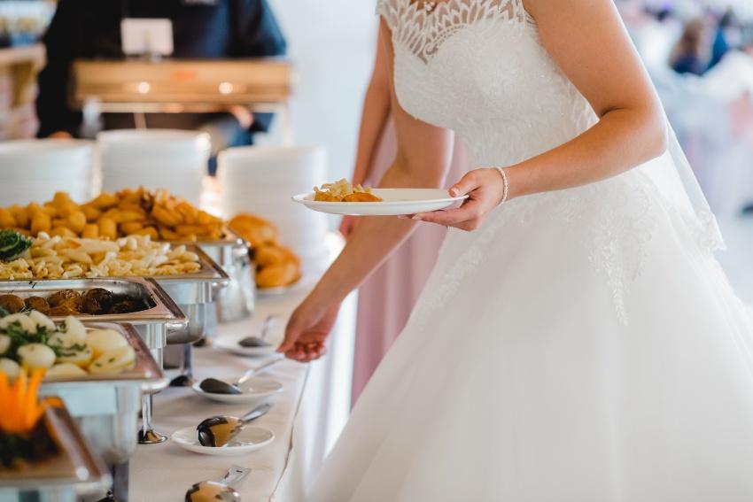 Braut bedient sich am Hochzeitsbuffet - Wie viel kostet eine Hochzeit