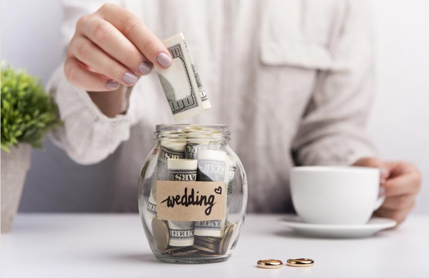 Frau gibt Geld in Hochzeitsspardose - Wie viel kostet eine Hochzeit