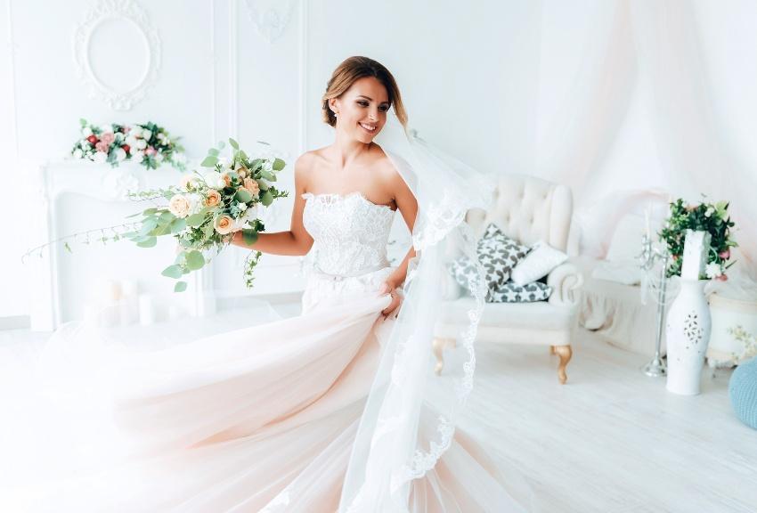 Braut in schönem Brautkleid und mit Blumenstrauß - Eco Wedding mit Second-Hand Brautkleid