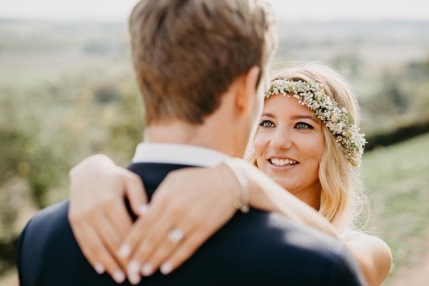 Ehepaar umarmt sich, Braut trägt einen Blumenkranz
