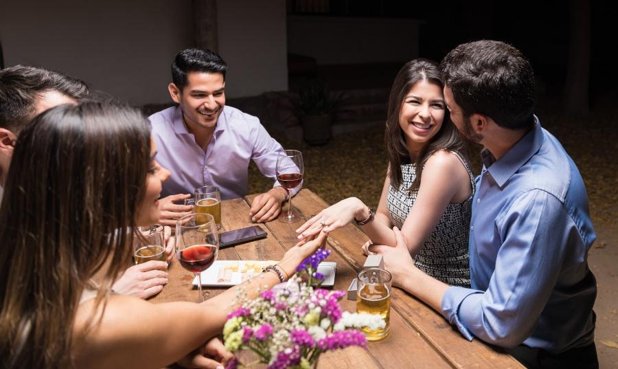 Verlobtes Paar feiert mit Freunden mit Wein