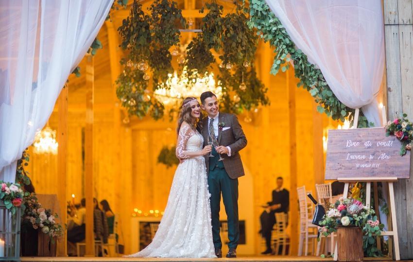 Hochzeitspaar steht in großer Scheune für eine moderne Landhochzeit