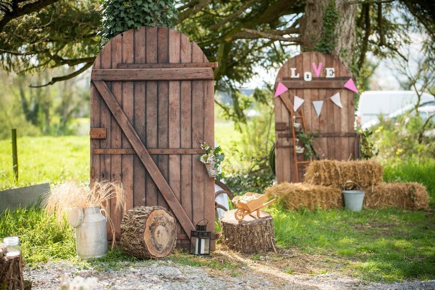 Zwei Scheunentore mit Hochzeitsdekoration und Strohballen für eine moderne Landhochzeit