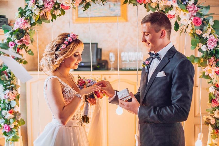 Ehemann steckt seiner Braut den Ehering an den Finger