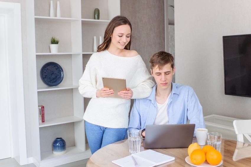 Junges Paar schaut auf Laptop - vielleicht planen sie eine Verlobungsfeier