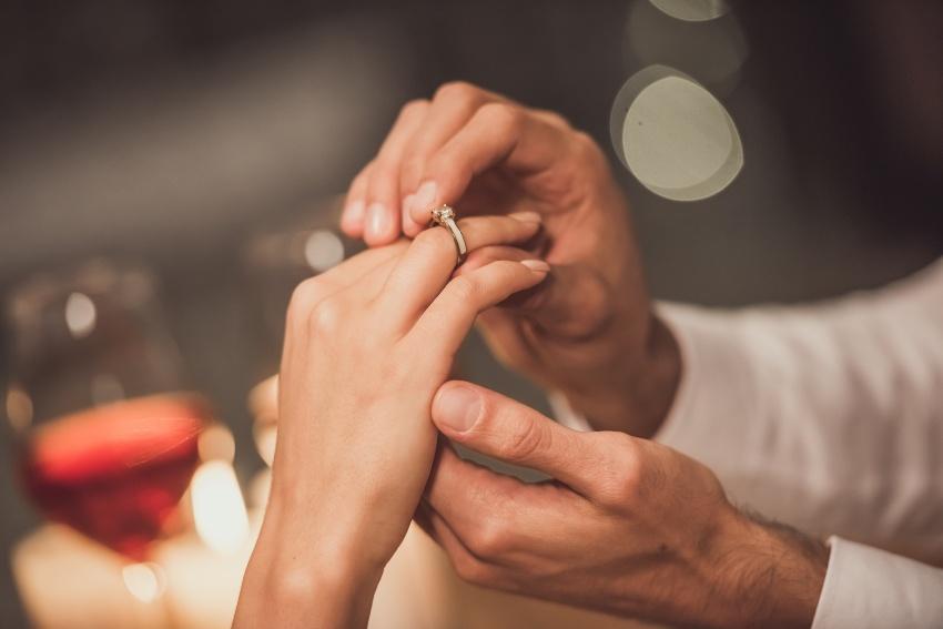 Mann steckt Frau den Verlobungsring an den Finger