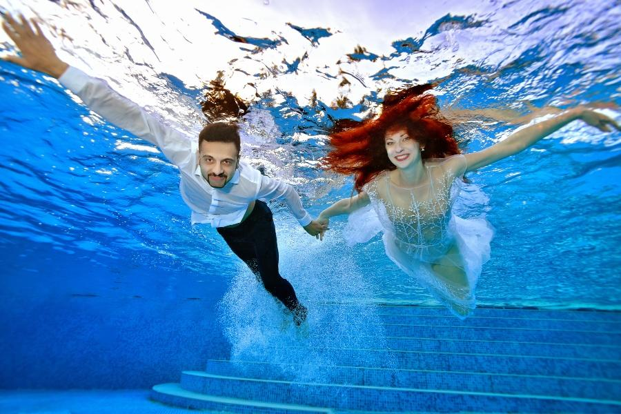 Paar in Hochzeitskleidung taucht im Pool - Die Hochzeit unter Wasser