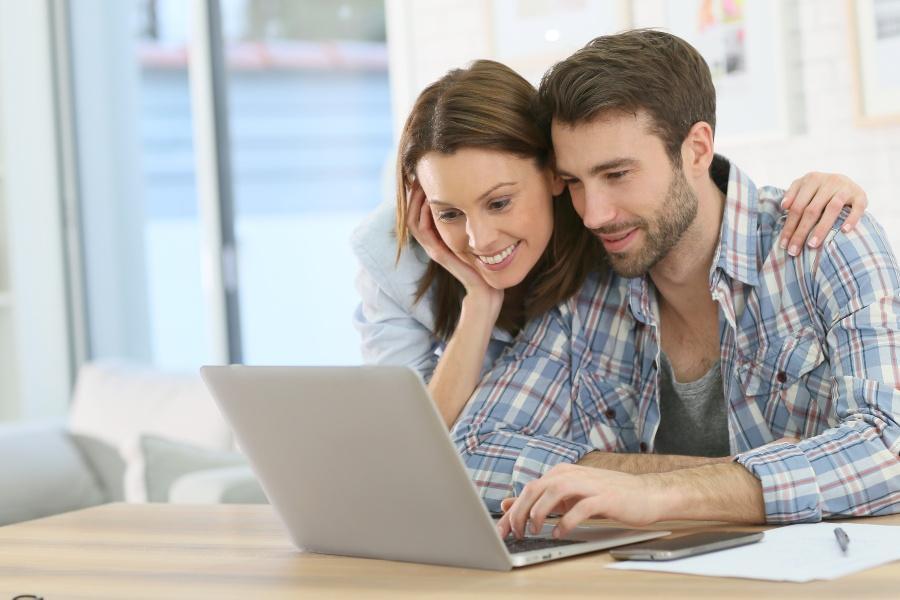 Junges Paar plant am Laptop die Hochzeit - die Zeit zwischen Verlobung und Hochzeit