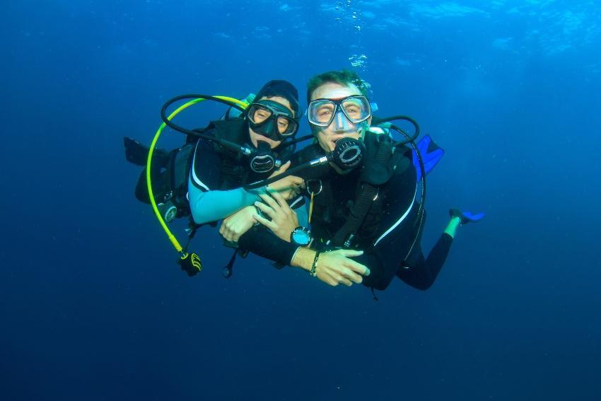 Glückliches Taucherpaar in Taucherausrüstung - Die Hochzeit unter Wasser