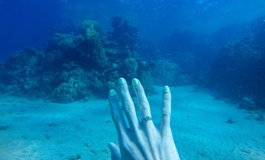 Frau unter Wasser zeigt Verlobungsring