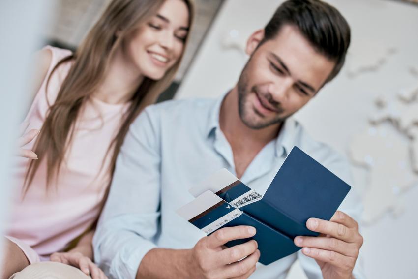 Ein junges Pärchen schaut auf Flugtickets und Visa